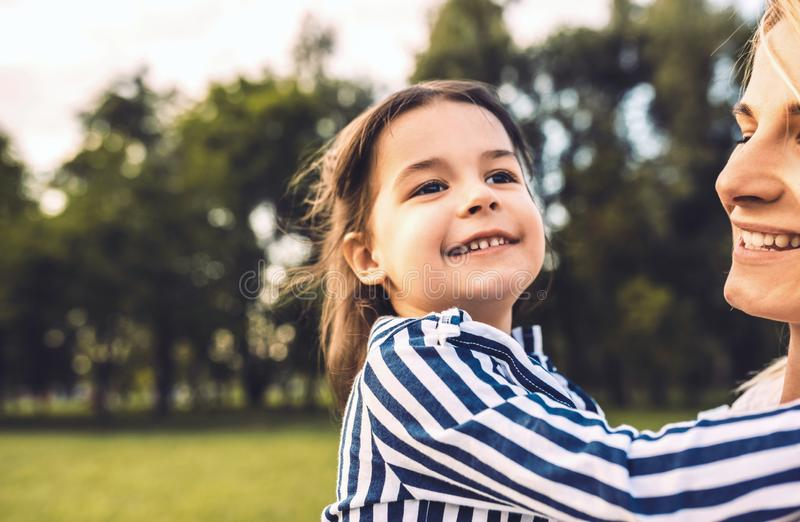 Beautiful happy little girl daughter embracing her mother in the park. Loving smiling mother and daughter spend time together in royalty free stock photography