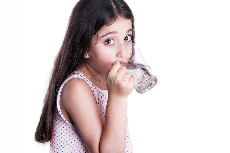 Beautiful happy little girl with long dark hair and dress holding glass of water. royalty free stock photo