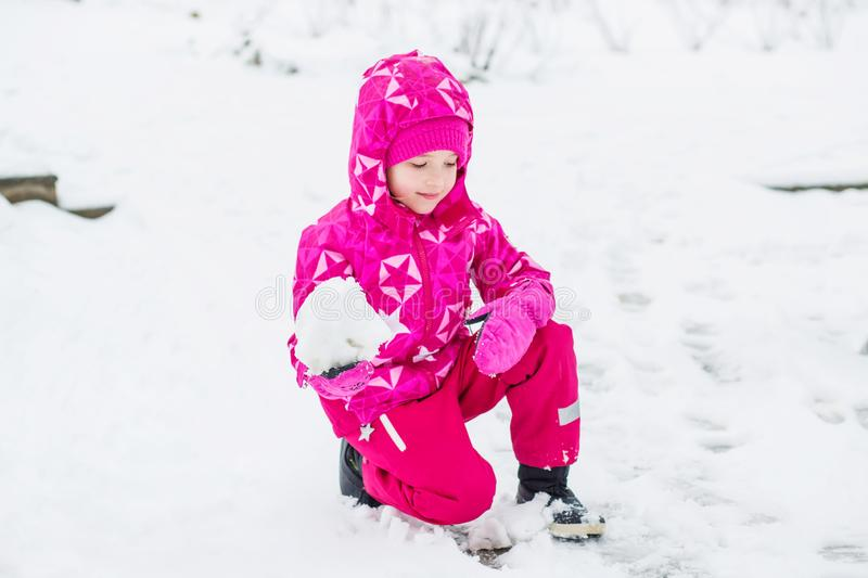 Beautiful happy little girl in pink winter clothes playing royalty free stock photos