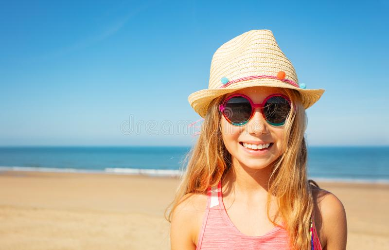 Beautiful happy little girl in straw hat on beach royalty free stock photo