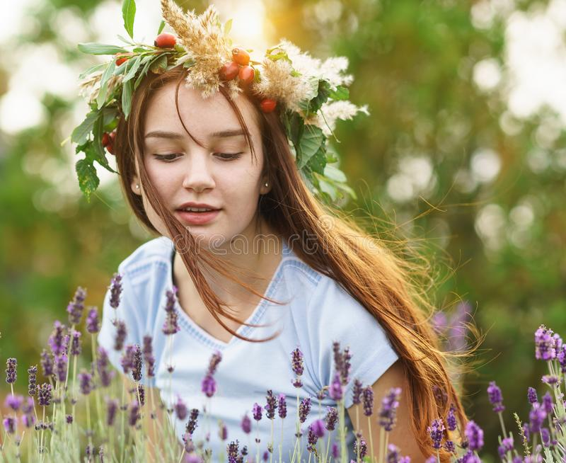 Beautiful happy long-haired girl in a wreath of flowers and berries. Portrait royalty free stock image