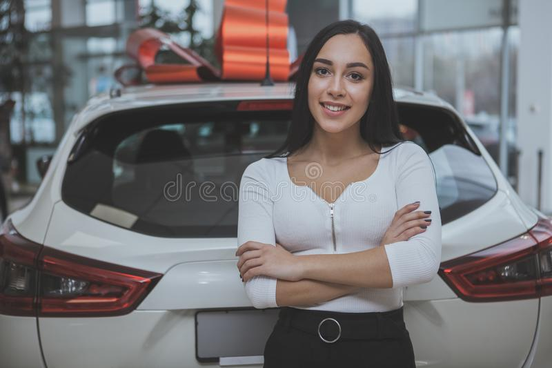 Lovely young woman buying new car at the dealership. Beautiful happy long haired woman smiling to the camera, posing proudly near her new car at the dealership royalty free stock images
