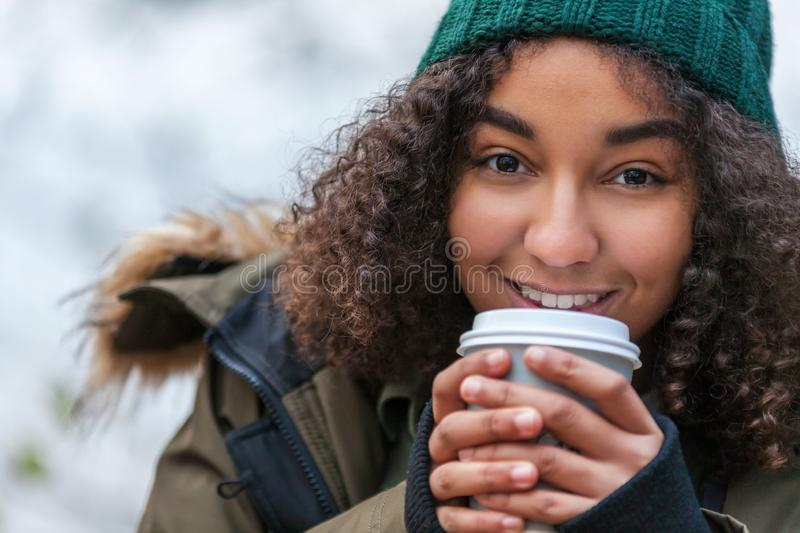 Mixed Race African American Teenager Woman Drinking Coffee. Beautiful happy mixed race African American girl teenager female young woman smiling drinking stock image