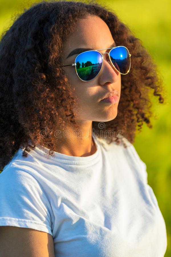 Mixed Race African American Girl Teen Sunglasses at Sunset. Beautiful and happy mixed race biracial African American female girl child teenager young woman in royalty free stock images