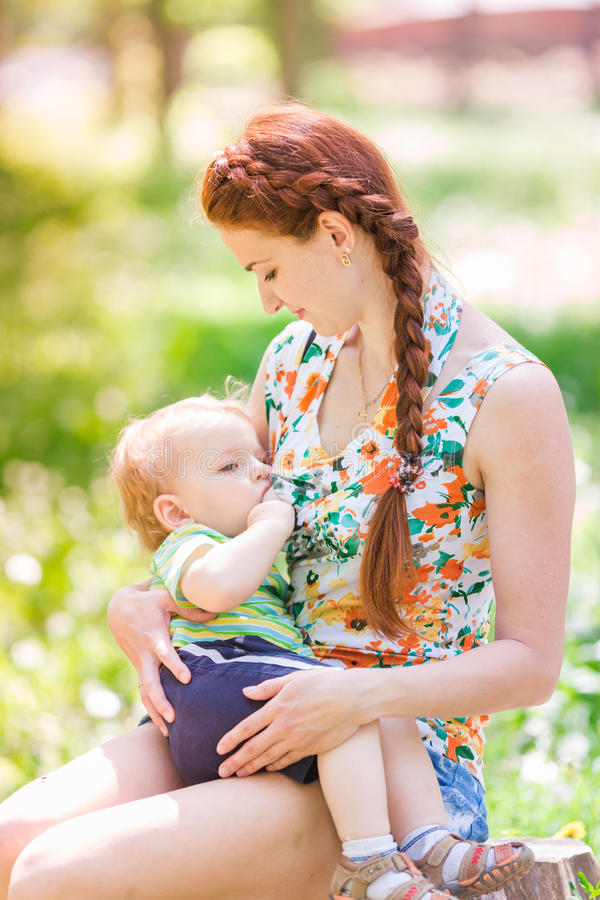 Beautiful happy mother breastfeeding outdoor stock photography