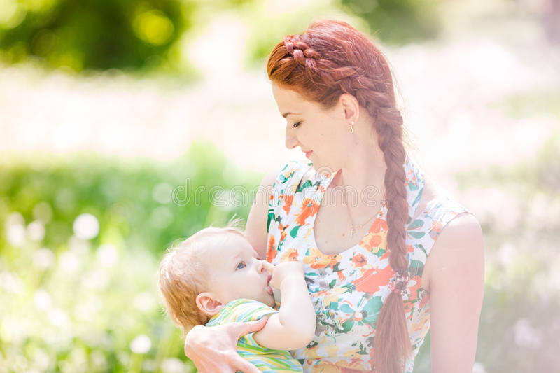 Beautiful happy mother breastfeeding outdoor stock image