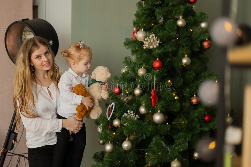 Beautiful happy mother with a daughter in her arms at the Christmas tree. Merry Christmas 2020. stock photography