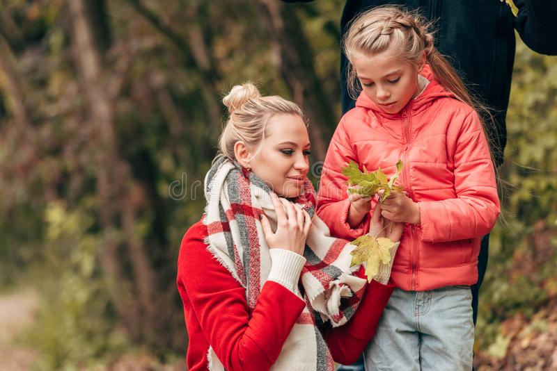 beautiful happy mother and daughter holding yellow leaves royalty free stock image