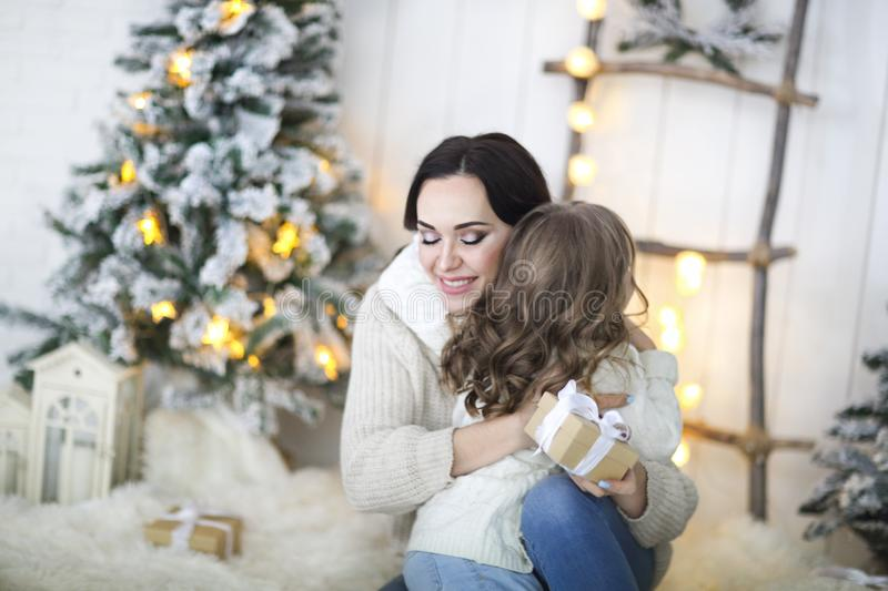 Beautiful happy mother with lher ittle daughter in knit sweater sitting on the background of Christmas interior stock photography