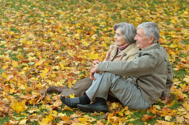 Beautiful happy old people. Sitting in the autumn park royalty free stock photo