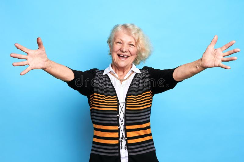 Beautiful happy old senior with open arms for hug looking at camera. royalty free stock image