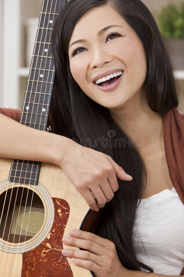 Beautiful Happy Oriental Woman Smiling & Guitar stock photo