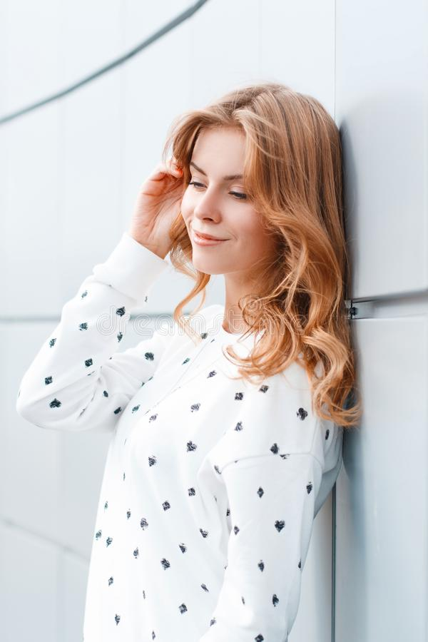 Beautiful happy positive young woman with fashionable hairstyle in a stylish white sweater resting near the modern wall. royalty free stock photography