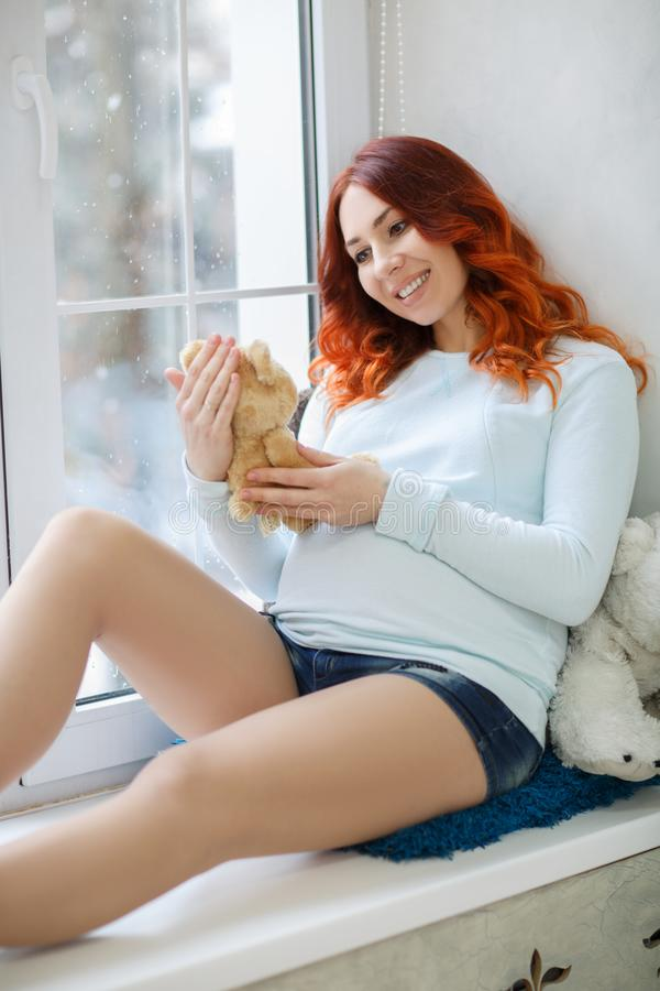Beautiful Happy Pregnant Woman Near the Window. Expectant mother in anticipation of her baby. Pregnant woman holding a toy bear in her hand in anticipation of royalty free stock photos