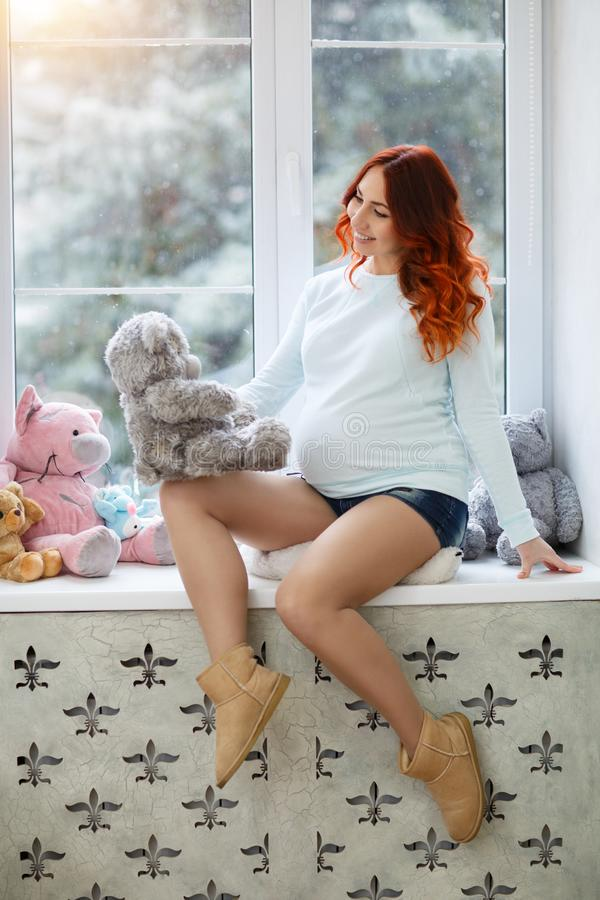 Beautiful happy pregnant woman near the window. Expectant mother in anticipation of her baby. Pregnant woman holding a toy bear in her hand in anticipation of royalty free stock photography