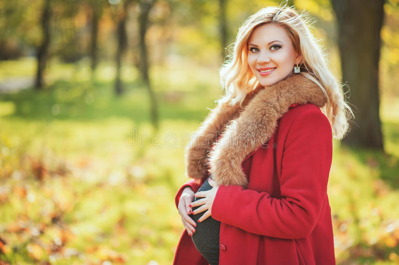 Beautiful happy pregnant woman staying in autumn park touching her belly and enjoying expecting of baby. royalty free stock photography