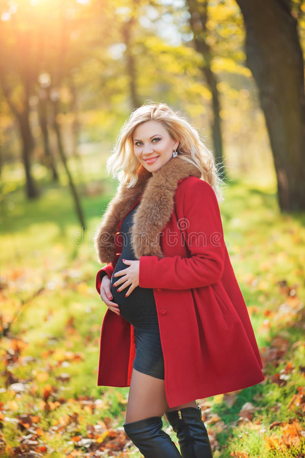 Beautiful happy pregnant woman staying in autumn park touching her belly and enjoying expecting of baby. stock photography