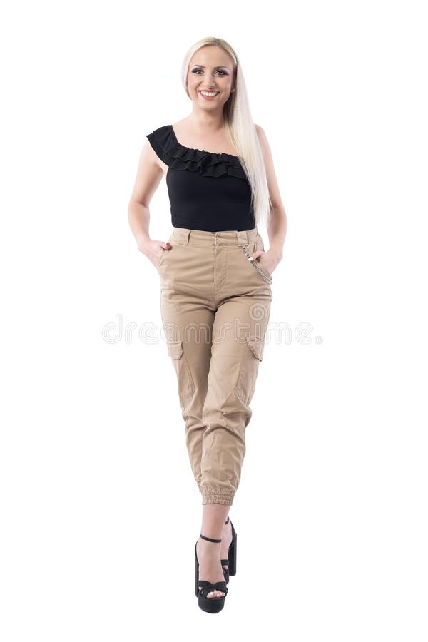 Beautiful happy smiling blonde woman in cream military pants and black top posing at camera. Full body isolated on white background stock image