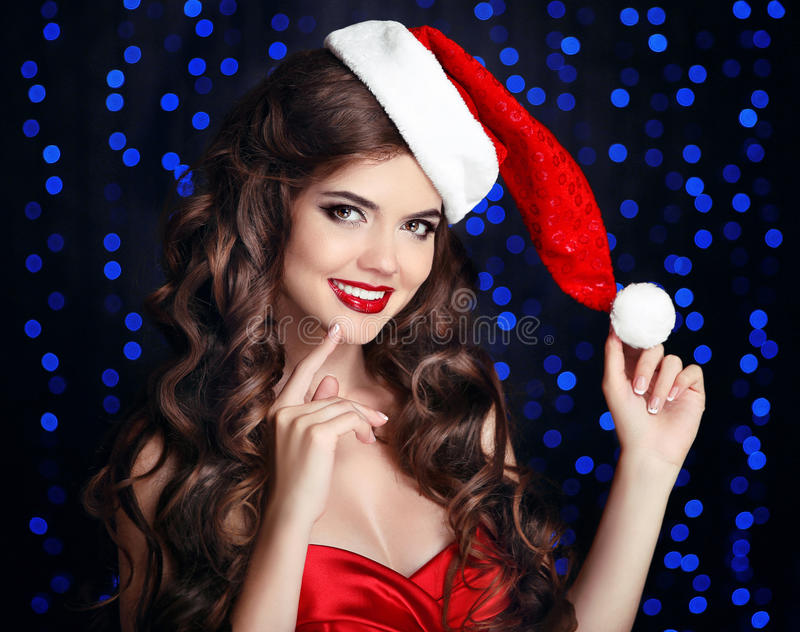 Beautiful happy smiling girl in santa hat with red lips posing f royalty free stock photography