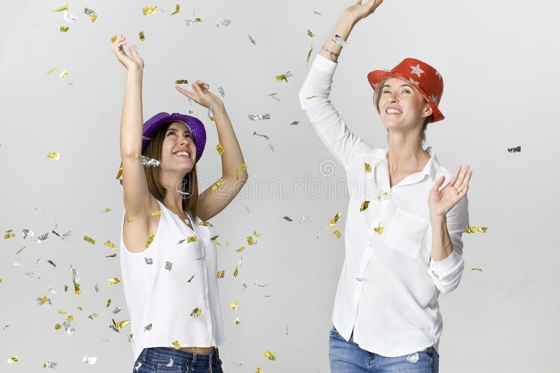 Happy dancing young female friends smiling with confetti against white background. Celebrating royalty free stock image