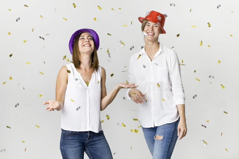 Happy dancing young female friends smiling with confetti against white background. Celebrating royalty free stock images