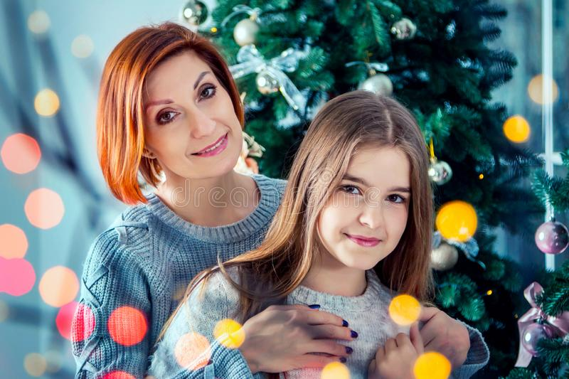 Beautiful happy smiling mother and daughter, standing near Christmas tree royalty free stock images