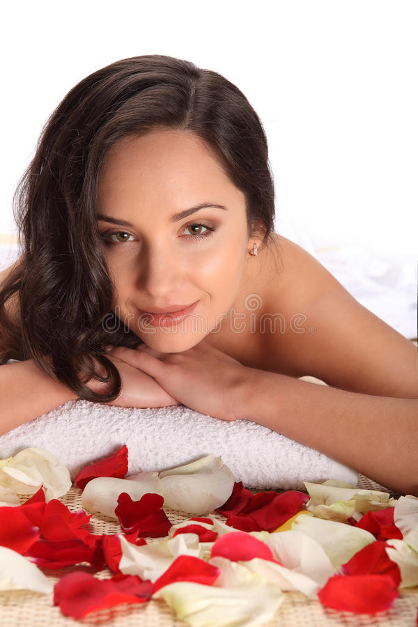 Beautiful happy smiling relaxed woman at health day spa, laying in white towel on bamboo table decorated with rose petals royalty free stock images