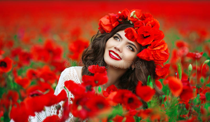 Beautiful happy smiling teen girl portrait with red flowers on h stock image