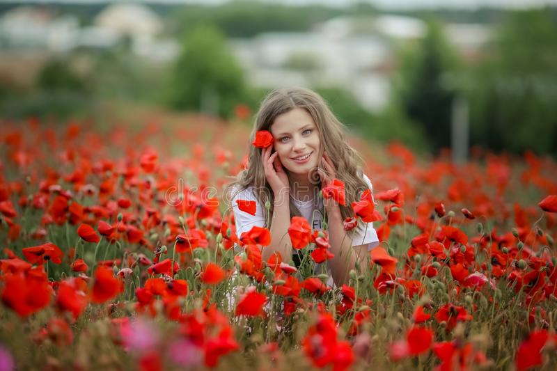 Beautiful happy smiling teen girl portrait with red flowers on head enjoying in poppies field nature background. Makeup royalty free stock images