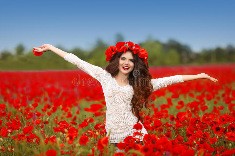 Beautiful happy smiling woman open arms in red poppy field nature background. Attractive brunette young girl model with curly. Hair and makeup laughing at stock photo