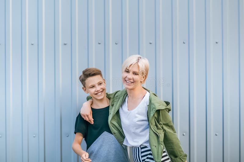 beautiful happy stylish mother and son laughing and embracing royalty free stock photos