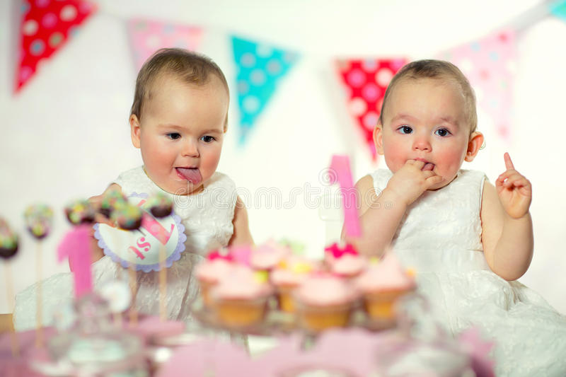 Beautiful happy twins baby on first birthday. Background royalty free stock photo