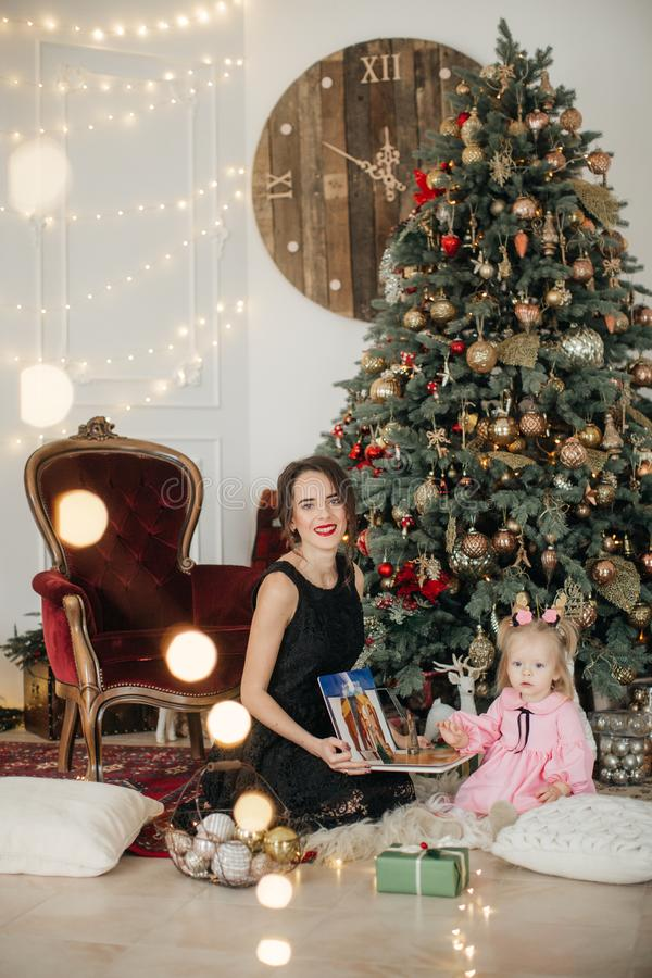 Beautiful happy woman with baby girl near a Christmas tree with gifts royalty free stock images