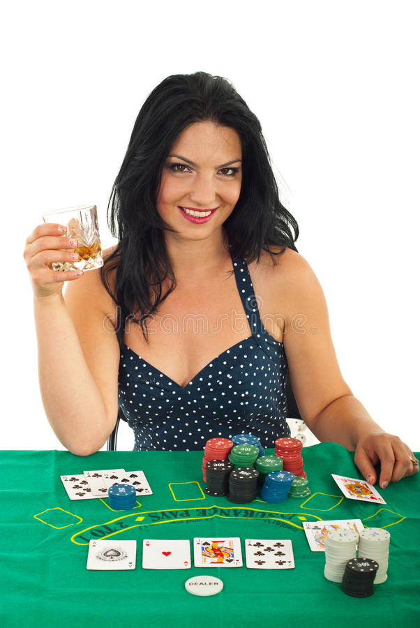 Beautiful happy woman at casino table. Beautiful happy brunette woman sitting at casino table and holding a glass with whiskey isolated on white background stock photos