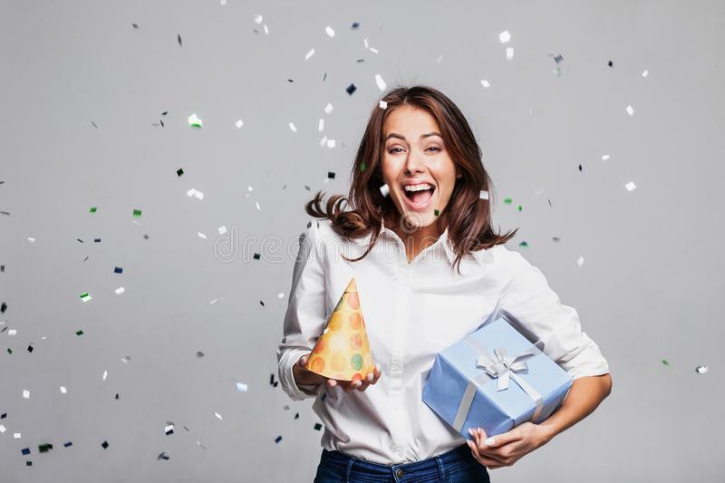 Beautiful happy woman at celebration party with confetti falling everywhere on her. Birthday or New Year eve celebrating concept. Studio shot royalty free stock photo