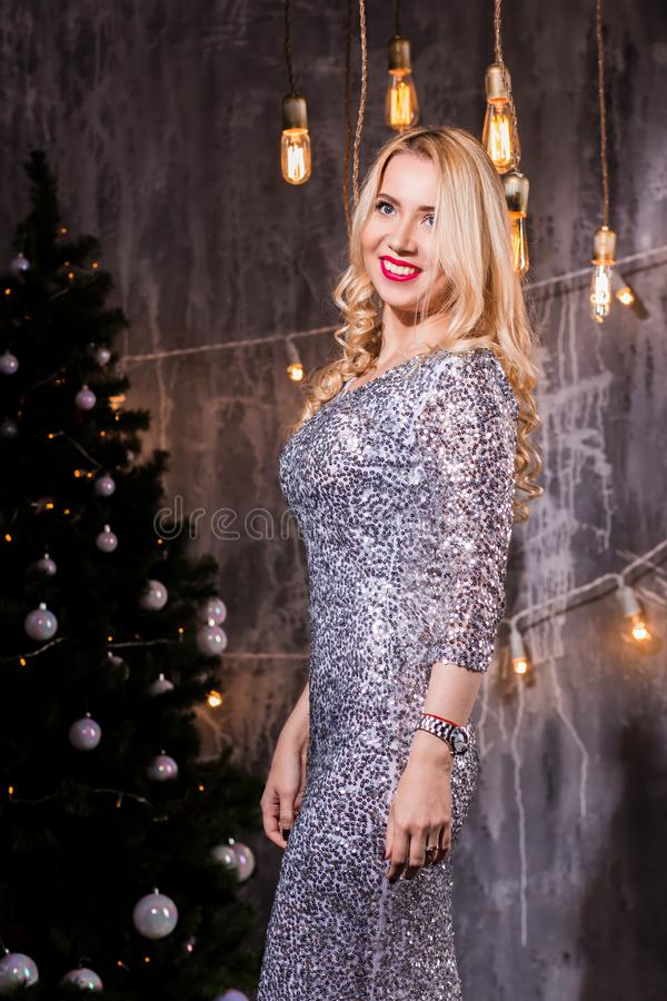 Beautiful happy woman at celebration party with confetti falling everywhere on her. New Year eve celebrating concept. Beautiful young elegant women in silver stock photography
