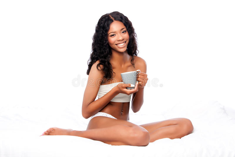 Beautiful happy woman with delicious coffee sitting in white bed royalty free stock image