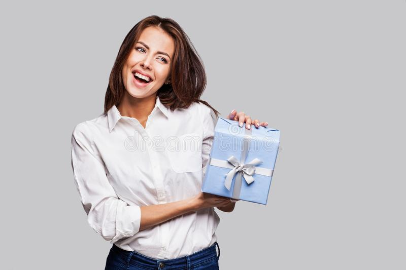 Beautiful happy woman with gift box at celebration party. Birthday or New Year eve celebrating concept. Studio shot stock photo