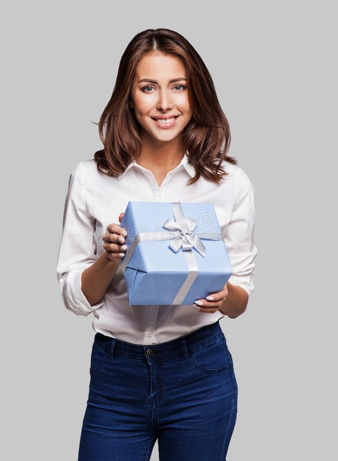 Beautiful happy woman with gift box at celebration party. Birthday or New Year eve celebrating concept. Studio shot royalty free stock image