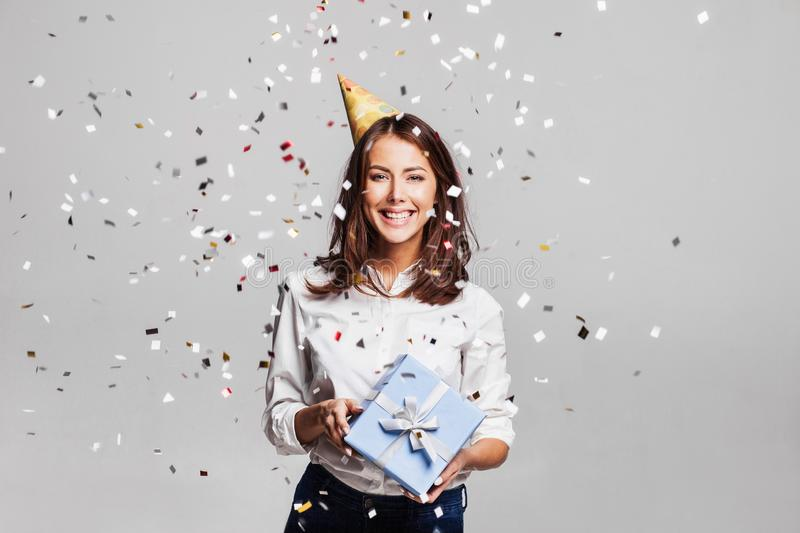 Beautiful happy woman with gift box at celebration party with confetti falling everywhere on her. Birthday or New Year eve celebrating concept royalty free stock image