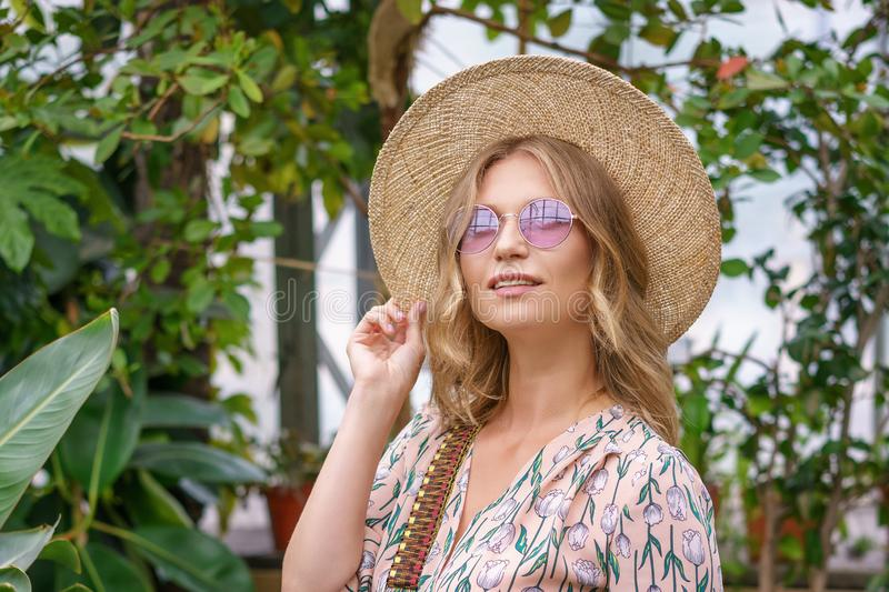 Beautiful happy woman with glasses and straw hat in the Park royalty free stock image