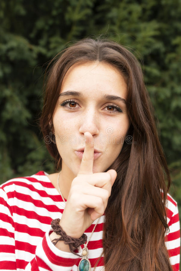 Beautiful happy woman has put forefinger to lips as sign of silence, outdoor. Happiness woman has put forefinger to lips as sign of silence stock photos