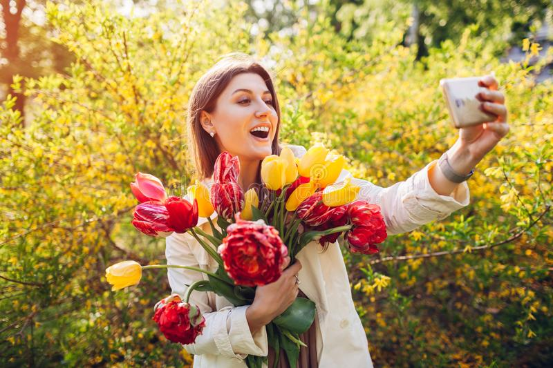 Beautiful happy woman holding bouquet of tulips and taking selfie. Girl having fun royalty free stock images