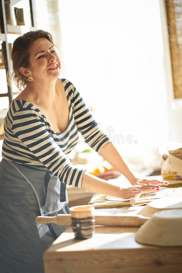 Beautiful happy woman making ceramic ware in workplace, laughing, smiling in sun light. Concept for woman in freelance, business royalty free stock photography