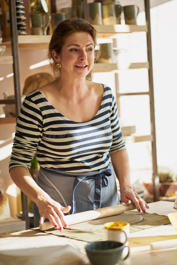 Beautiful happy  woman making ceramic ware in workplace, smiling in sun light. Concept for woman in freelance, business, hobby stock photography