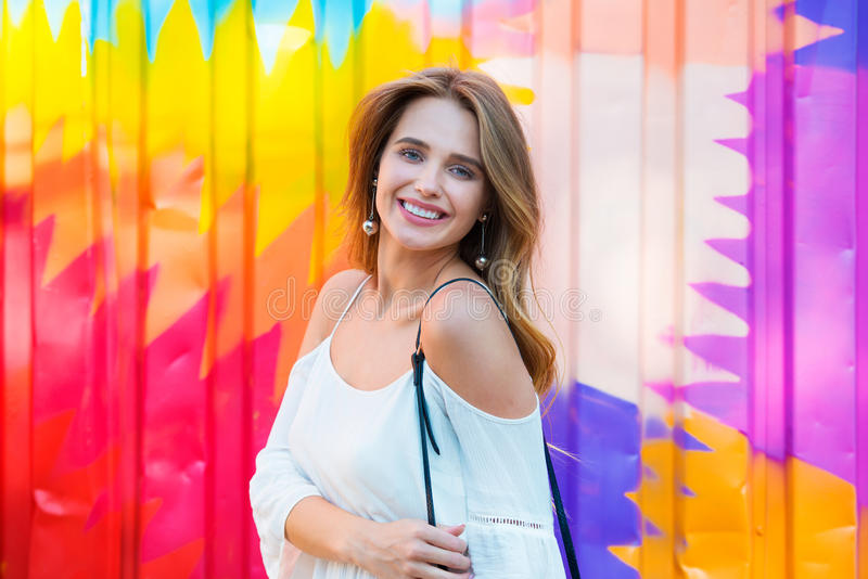 Beautiful happy woman with perfect smile posing agains colorful metal wall and looking into camera stock images