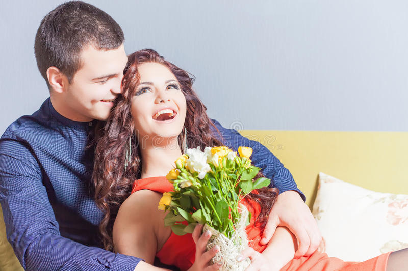 Beautiful happy woman received a flower bouquet of roses. Beautiful happy women received a flower bouquet of chinese roses. Boyfriend gave flowers. Love. Couple royalty free stock image