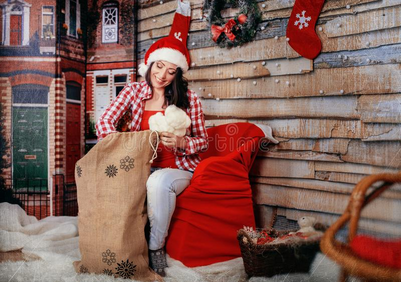 Beautiful happy woman in red shirt gets gifts from the bag. The royalty free stock photo