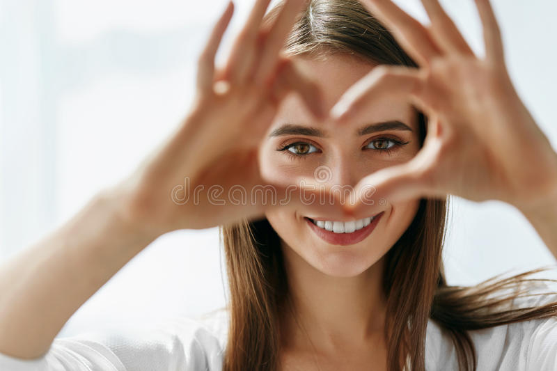 Beautiful Happy Woman Showing Love Sign Near Eyes. Healthy Eyes And Vision. Portrait Of Beautiful Happy Woman Holding Heart Shaped Hands Near Eyes. Closeup Of