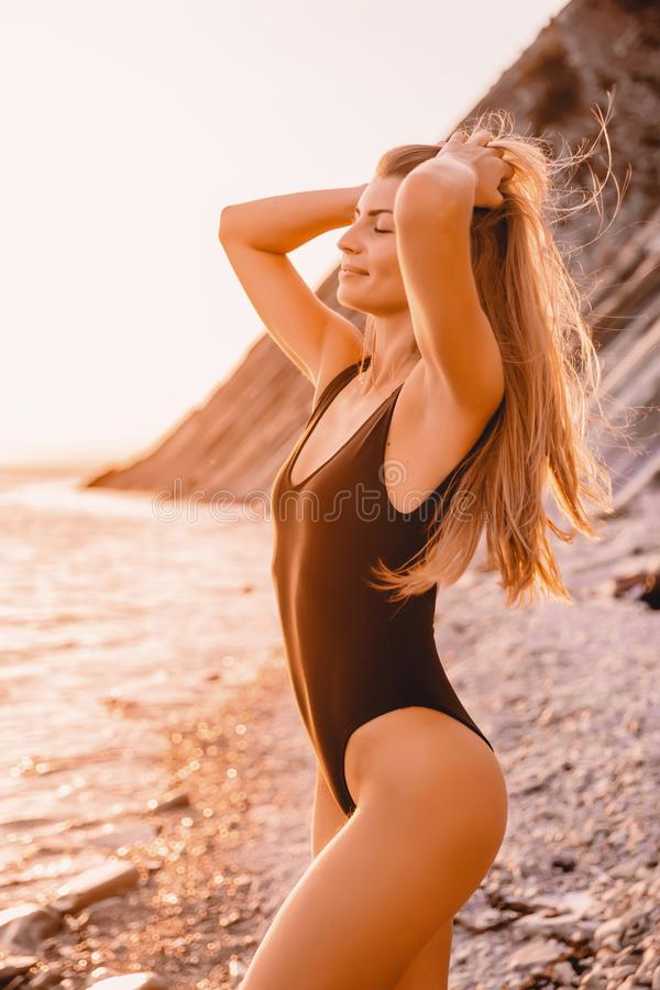 Beautiful happy woman in stylish swimwear on stones beach with warm sunset colors. royalty free stock photography